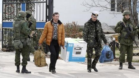 Oficiales ucranianos abandonan con sus pertenencias la sede del Cuartel General de la marina ucraniana en Sebastopol a orillas del Mar Negro.