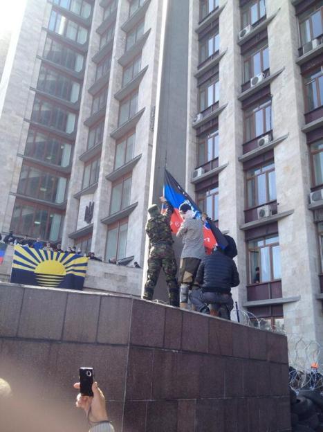 Manifestantes colocan la bandera de la República Popular de Donetsk en el edificio de la Administración