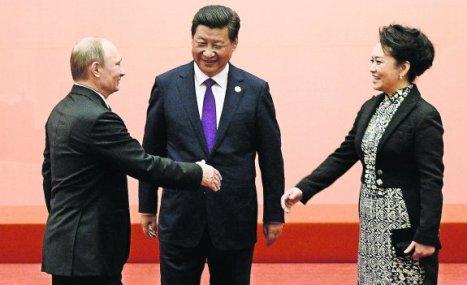 Putin saluda a la primera dama china, Peng Liyuan, ante la mirada del presidente Xi Jinping en la conferencia asiática de Shanghái.  Foto: REUTERS.