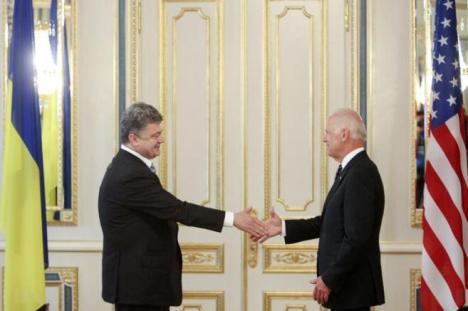 El nuevo presidente ucraniano Petro Poroshenko le da la mano a Joe Biden, vicepresidente de EEUU.  FOTO: REUTERS.